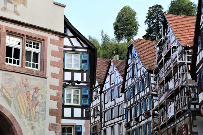 Eine gepflegte Zeile von historischen Fachwerkhäusern an dem Aufstieg zum Schlossberg. Links im Bild das Schiltacher Rathaus mit einer Darstellung des Flößer-Handwerkes.