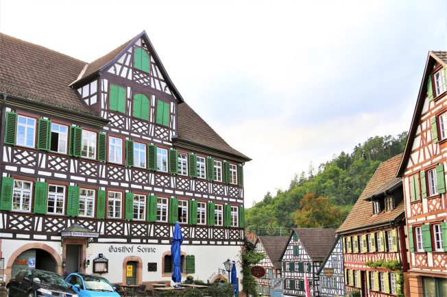 """Der Gasthof Sonne wurde bereits im 17ten Jahrhundert erbaut. Sein Standort, direkt an der Fernhandelsstraße von Straßburg auf die Alp nach Rottweil, praktisch dem Verlauf der alten Römerstraße """"Arae Flaviae"""" folgend, war ideal für die Reisenden. Die Pferde-Fuhrwerke mussten hier vorspannen, um den steilen Anstieg zum Schlossberg zu bewältigen, nachdem sie die Furt durch die Schiltach geschafft hatten. Links unten im Bild erkennt man das Rundbogentor des alten Pferdestalles, in dem Vorspann -Pferde untergebracht waren."""